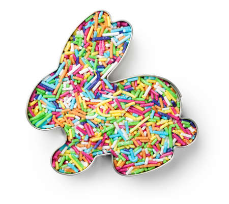 Colorful candy sprinkles in cutter in shape of bunny on white background. Top view Stock Photo