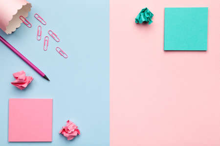 Sticky notes with crumbled paper balls and office accessories on pastel background. Minimal style. Flat lay. Copy space. Top view Stock Photo