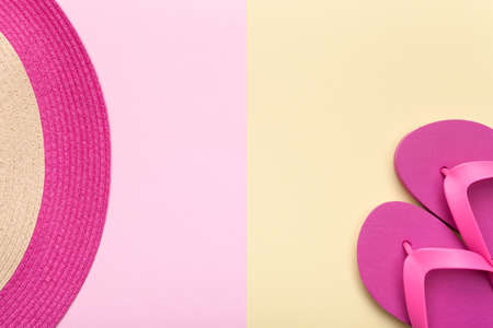 background: Summer concept. Beach hat and flip flops on pink and yellow background. Flat lay. Minimal style. Stock Photo