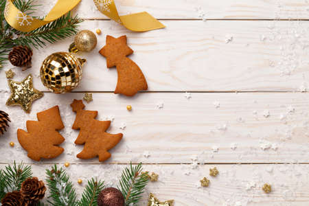 Christmas composition with gingerbreads on wooden background. Copy space. Top view