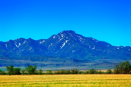 Blue sky over the mountains and yellow steppe Stock Photo
