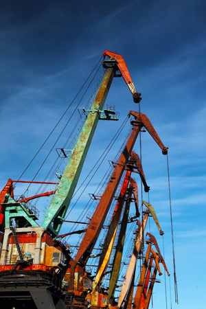 Old port cranes on the blu sky background photo