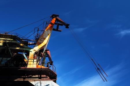Old port cranes on the blu sky background photo