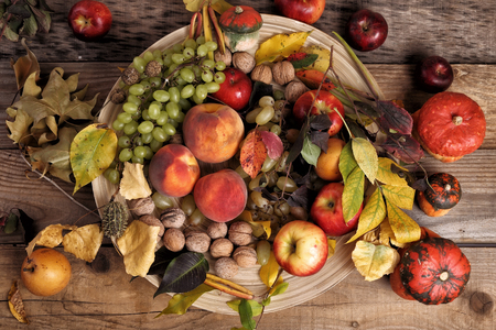 autumn still life of fruits, nuts and leaves with wood plate on a wood table photo