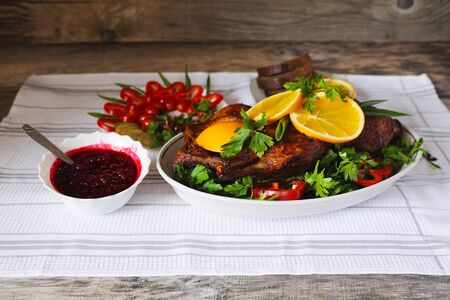 Roasted duck with orange, berry sauce, vegetables and bread  on a wood table photo