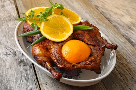 Roasted duck with orange on a wood table photo