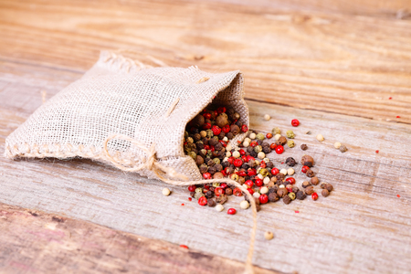Pepper mix in a sack on the wood table photo