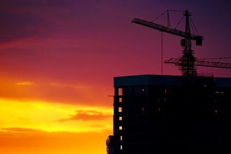 Industrial construction crane and building silhouettes over sunset photo