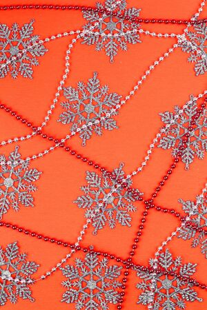 necklase: Orange paper background with the sparkling snowflakes and beads