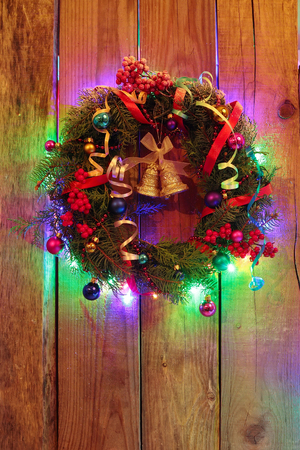 Christmas wreath with golden bells and christmas lights on the wooden background Stock Photo - 24354835