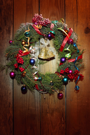 Christmas wreath with golden bells on the wooden background photo