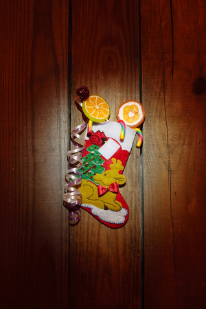 Christmas sock with candies on the wooden background, close up photo