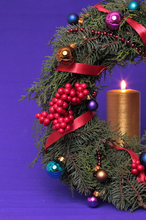 Christmas advent wreath with burning candle, close up photo