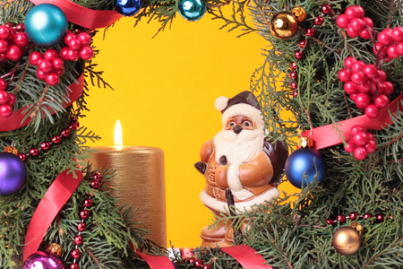 Christmas advent wreath with burning candle and santa figurine, close up photo