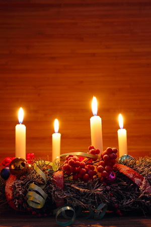 Advent wreath of twigs with four burning white candles and decorations photo