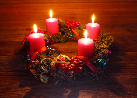 Advent wreath of twigs with four burning red candles and decorations photo