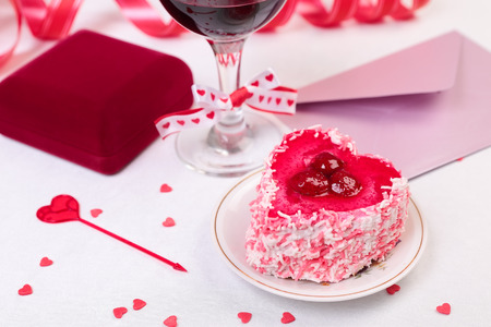 Valentine day still-life with cake, glass of wine, gift box and decorations photo