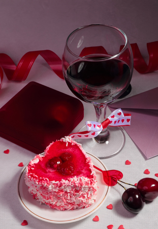 wine gift: Valentine day still-life with cake, glass of wine, gift box and decorations