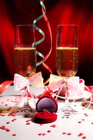 Glasses of champagne with the ring in gift box and Valentine Day decorations photo