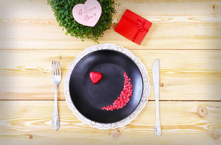 Still-life with heart on a plate and valentine decorations Stock Photo - 25191619