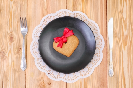 Heart shaped gingerbread cookie on the black plate, top view photo