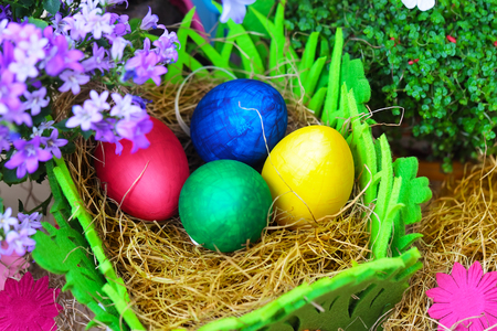 Four colorful easter eggs in a natural straw with flowers, close up photo