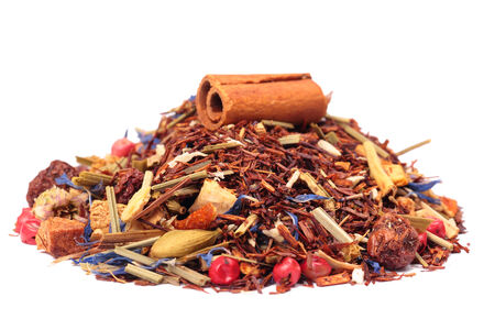rooibos tea with cinnamon and fruits isolated on the white background, selective focus