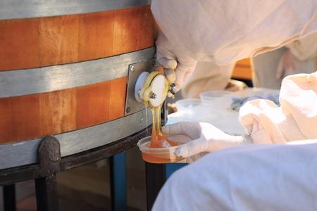 Mann gießt Honig aus dem Fass, close up