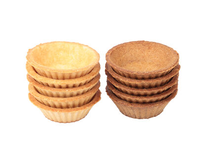 tartlet: A stack of empty light and dark tartlets on white background