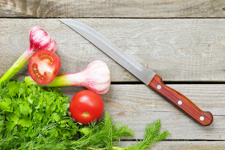 Vegetables, greens and knife on a wood table Stock Photo