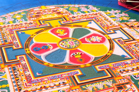 Tibetian monks constructing mandala from colored sand
