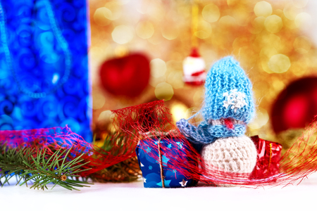 Little snowman figurine and gift boxes on the christmas decorations background photo