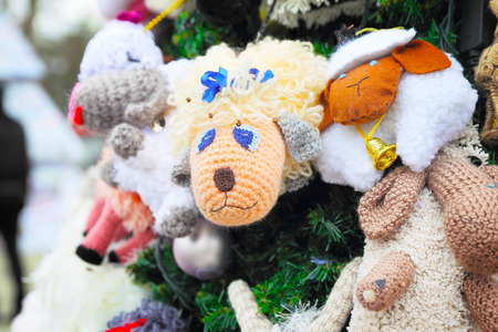 Fragment of christmas tree decorated with sheep toys, close up photo
