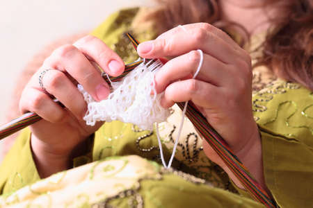 purl: Close-up of woman hands knitting with stylish knitting needles