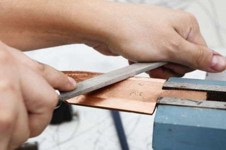 billet: Grinding the copper billet with a file, close up