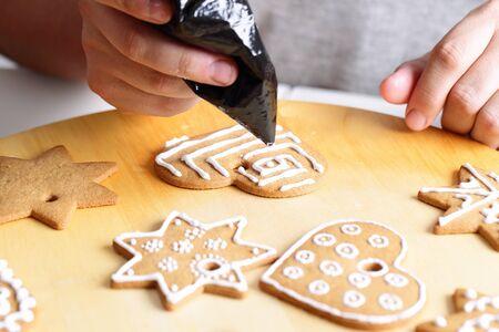 decoracion de pasteles: Mujer decorar galletas de jengibre. Cierre de vista con un enfoque selectivo.