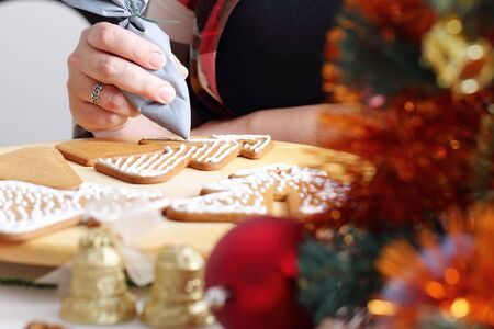 decorating christmas tree: Woman decorating gingerbread cookies in the shape of Christmas tree. Close up view with selective focus.
