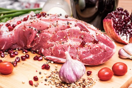 Raw meat on a cutting board with spices. Stock Photo