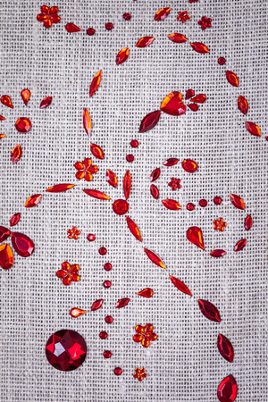 red sequins floral ornament on the linen fabric texture