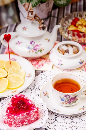 Porcelain cup of tea with lemon and sweets