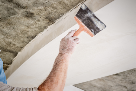 manual worker with wall plastering tools Stock Photo