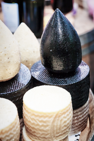 Black cheese with different types of delicious cheese close up
