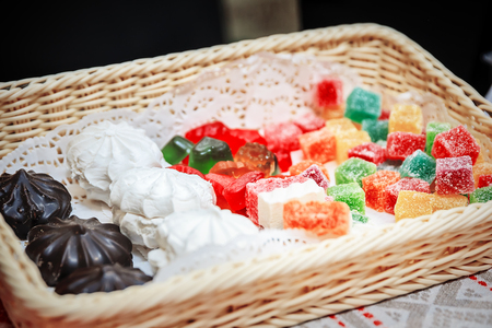 Assortment of homemade confectionery in the wicker basket. Marshmallow, zephyr, marmalade, jelly Stock Photo