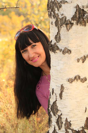The beautiful dark-haired girl  is looking out because of a birch photo