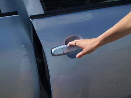 The female hand opening a door of the car     photo