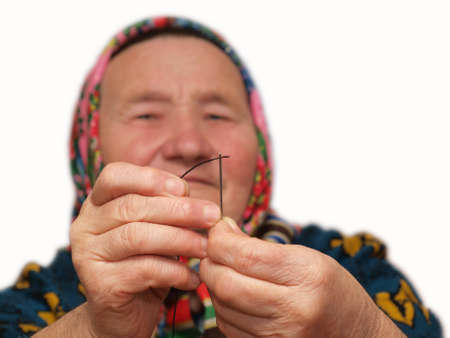 elusive: The elderly woman inserting a thread in a needle Stock Photo