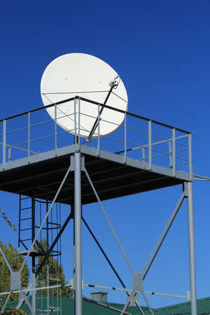 dish disk: The satellite television white round aerial on blue Stock Photo