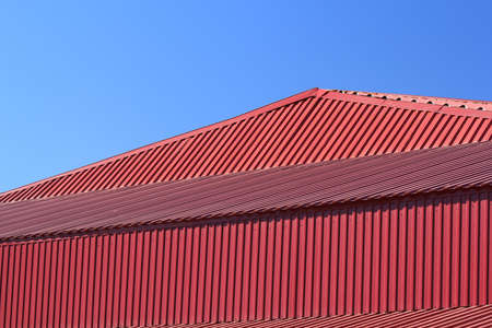 red metal: Fragment of the red metal roof of the house on blue