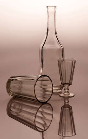 Glass-ware on reflective surface. Bottle, wine-glass and glass Stock Photo