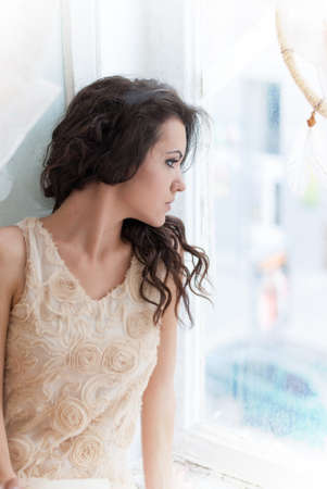 Beautiful young brunette woman looking out the window, natural light Stock Photo
